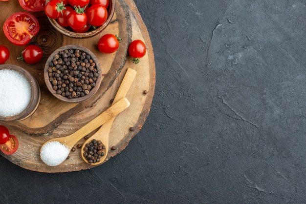 Close up view of fresh tomatoes and spices on wooden board on the right side on black surface with free space