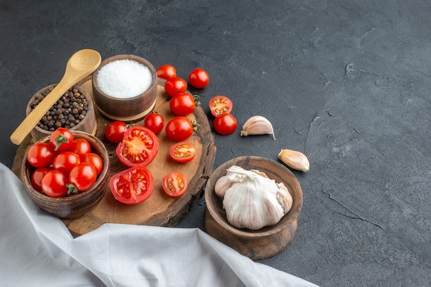 Vista ravvicinata di pomodori freschi e spezie su tavola di legno asciugamano bianco garlics su superficie nera