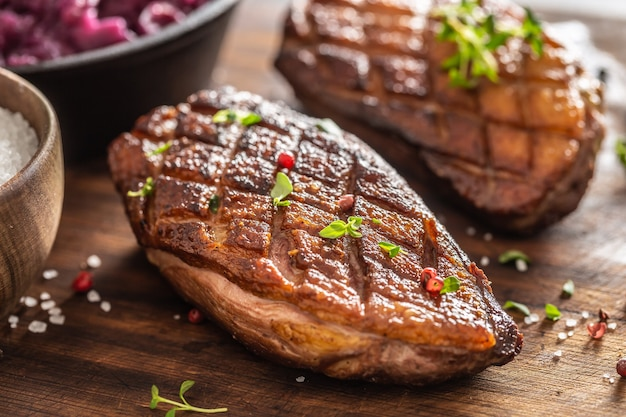 Close up view of freshly roasted duck breasts with pepper seasoning and fresh herbs on top.