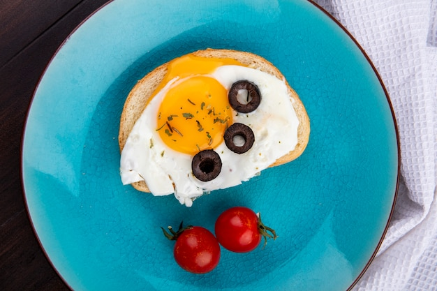 Close up view of fried egg with black olive slices on bread slice and tomatoes in plate on white cloth on wooden wall