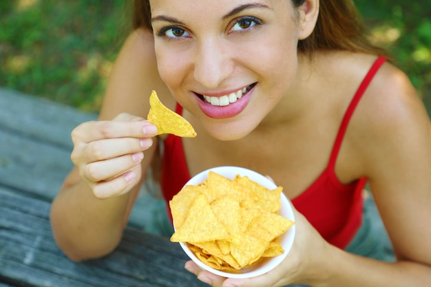 Крупным планом вид сверху красивой молодой женщины есть чипсы тортильи открытый.