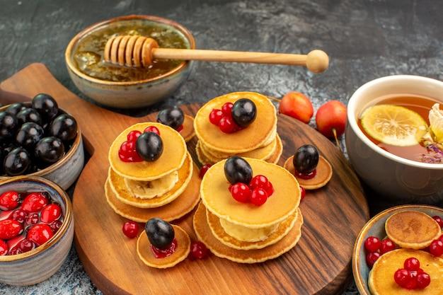 Vista ravvicinata di frittelle di frutta servite con miele una tazza di tè