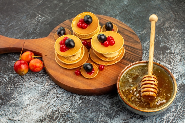 Close up view of fruit pancakes on wooden cutting board honey in a white bowl on gray