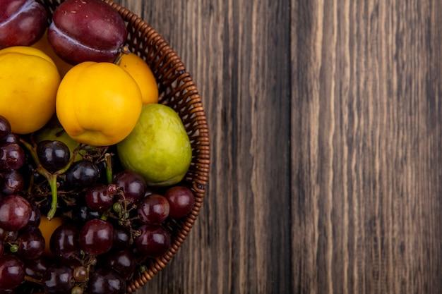 Vista ravvicinata di frutti come uva pluots nectacots nel cesto su sfondo di legno con copia spazio