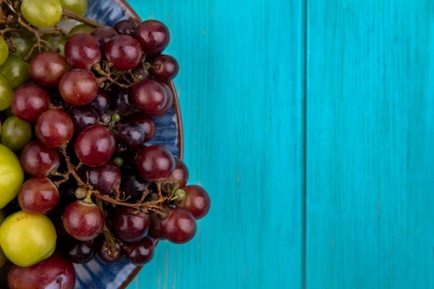 Vista ravvicinata di frutti come prugne e uva nel piatto su sfondo blu con copia spazio