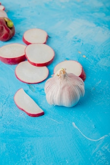 Close-up view of garlic with sliced radish on blue background with copy space