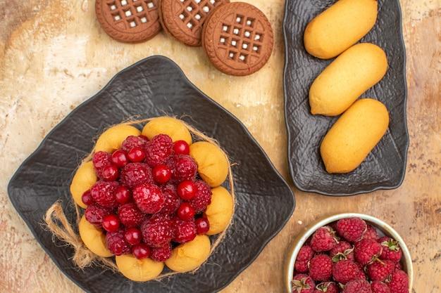 Vista ravvicinata di una torta regalo e biscotti sulla piastra marrone sulla tabella dei colori misti