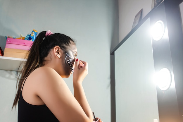 Close-up view of a girl concentrating on making up an artistic skull for halloween in her room.