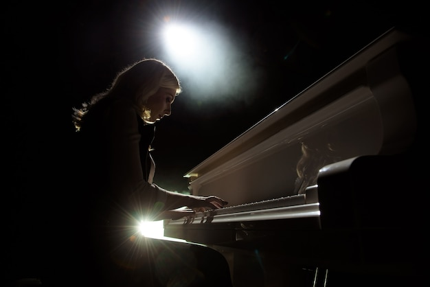 Close up view of a girl plays piano in the concert hall at the scene