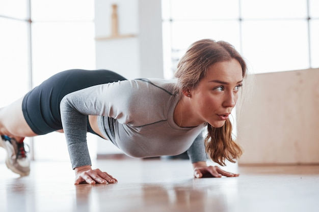Close up view of girl that does some exercises. sportive young woman have fitness day in the gym at morning time
