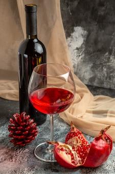 Vista ravvicinata di un bicchiere e una bottiglia con un delizioso vino rosso secco e un cono di conifere di melograno aperto su sfondo di ghiaccio