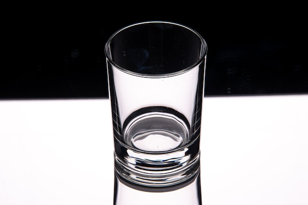 Close up view of glass cup on white table on dark background with free space