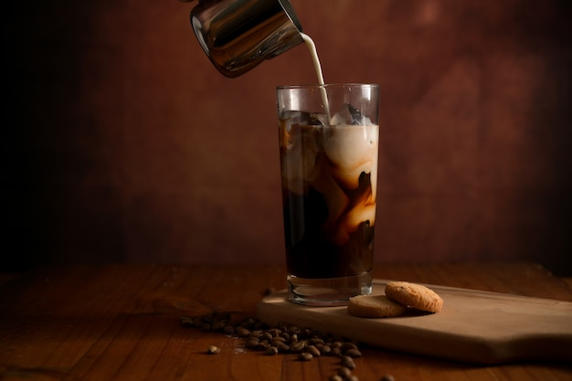 Close up view of a glass of ice coffee while adding milk with biscuit and coffee beans on wooden table