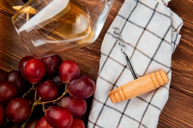 Vista ravvicinata di un bicchiere di vino bianco e uva con cavatappi sul panno sul tavolo di legno