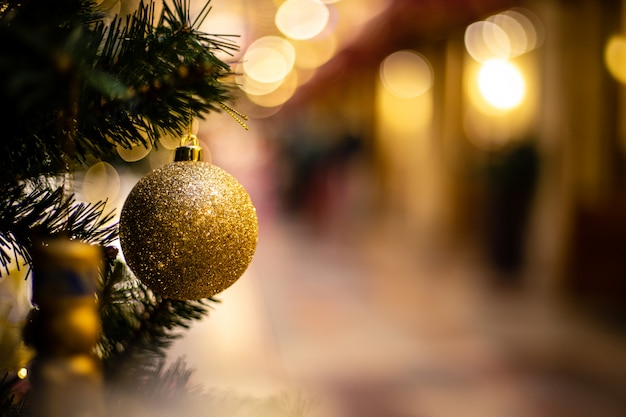 Close-up view of golden ball as decoration hanging on the branches of a christmas tree and sparkling in the sunshine.