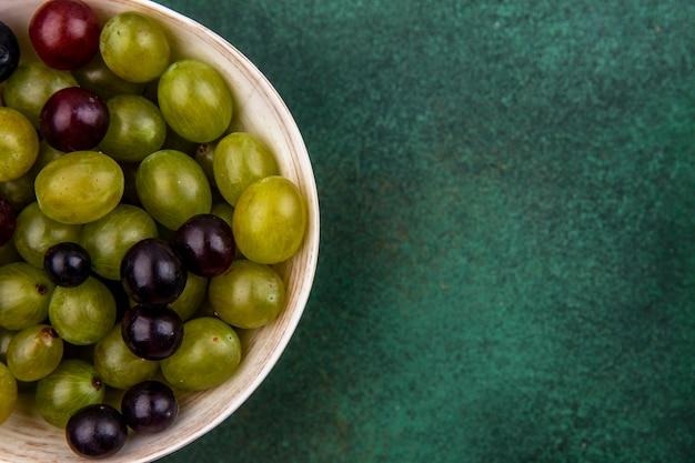 Vista ravvicinata di acini d'uva nella ciotola su sfondo verde con spazio di copia