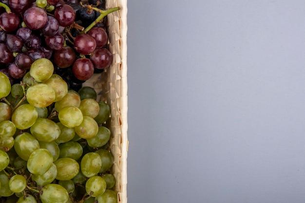 Vista ravvicinata di uva nel cesto su sfondo grigio con copia spazio