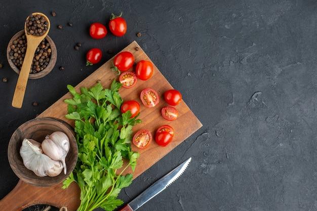 Vista ravvicinata del fascio verde fresco intero di pomodori tagliati aglio su tagliere di legno coltello pepe su superficie nera angosciata