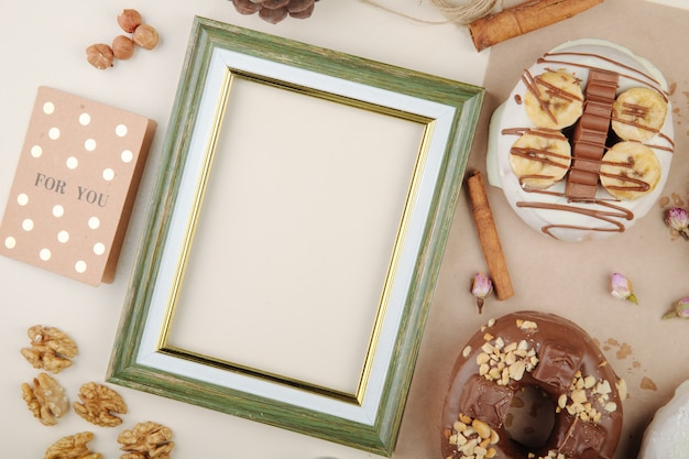 Close-up view of green frame with cinnamon cookies nuts on white with copy space