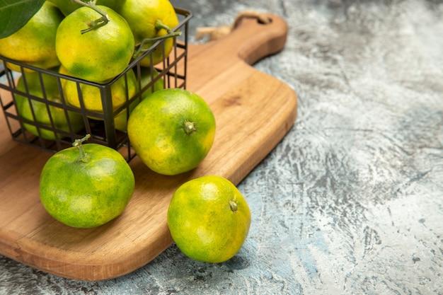 Vista ravvicinata di mandarini verdi con foglie all'interno e all'esterno di un cesto su tagliere di legno su tavolo grigio