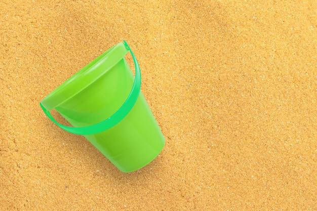모래 해변에 고립 된 보기 녹색 모래 양동이를 닫습니다. 텍스트 복사 공간을 추가했습니다.