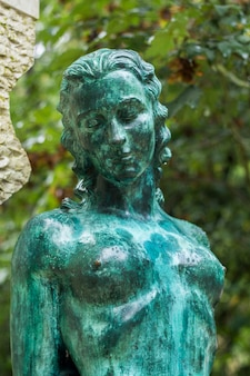 Close up view of a green statue of a naked woman.