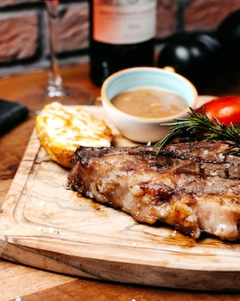 Close up view of griled beef steak served with vegetables and sauce on wooden board