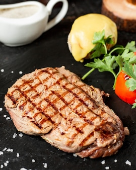 Close up view of grilled beef steak served with vegetables parsley and sauce on black board