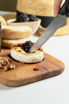 Close up view on grilled camembert with blackberry jam, nuts and chiabatta on grey background. copy space. cheese. tasty food for lunch. soft focus. food for wine