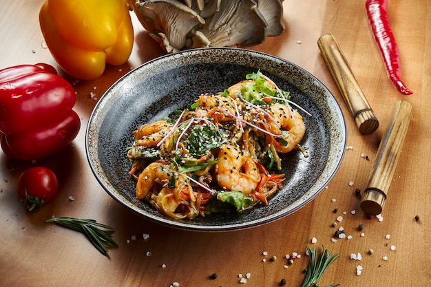 Close up view on grilled tiger prawns and scallops with pasta udon in a black bowl on a wooden surface