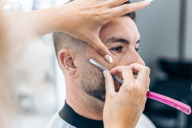 Close up view of a hairdresser shaving a caucasian man with a razor in a salon