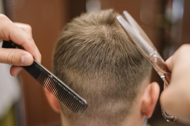 Vista del primo piano del parrucchiere che dà un taglio di capelli ad un cliente