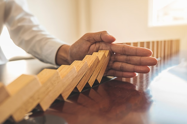 Close up view on hand of business woman stopping falling blocks on table.