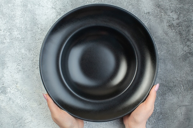 Close up view of hand holding black dinnerware set on isolated gray ice surface with free space