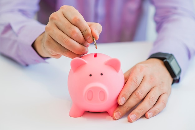 Close up view of the hand of a man placing a coin into the slot of a piggy bank in a savings and investment concept