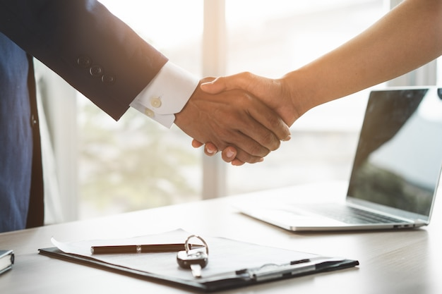 Крупным планом зрения рука агента, давая ключ от машины клиенту после подписания формы договора аренды.
