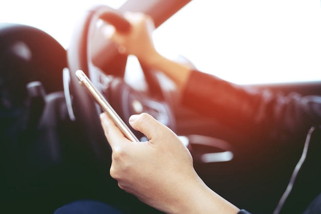 Close up view hand satisfied young businessman looking at mobile smart phone  while driver a car. transportation and vehicle concept.