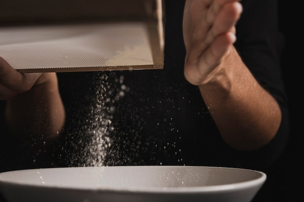 Close-up view hand sifting flour
