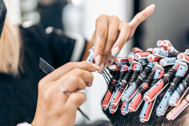 Close up view of a hands of a caucasian hairdresser fixing a client's hair with rollers to dye it