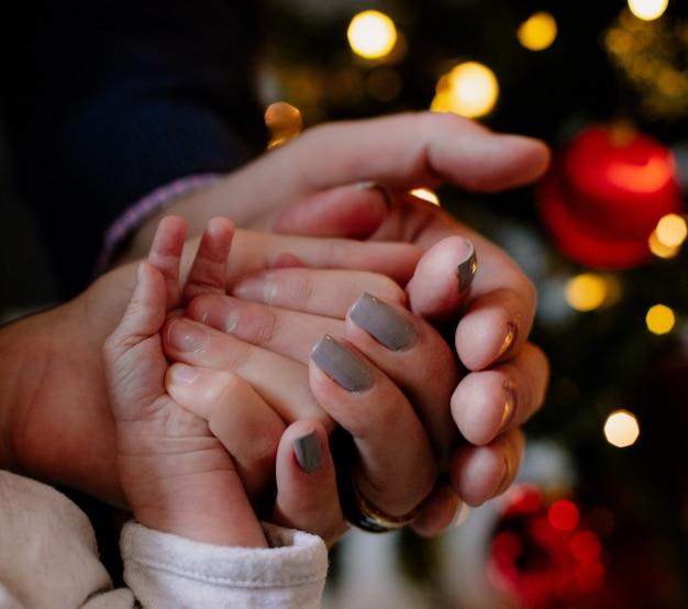 Vista ravvicinata delle mani di padre madre e dei loro figli insieme a casa nel periodo natalizio intorno all'albero di natale