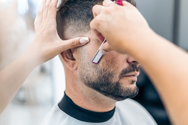 Close up view of the hands of a hairdresser shaving a man with a razor in a salon