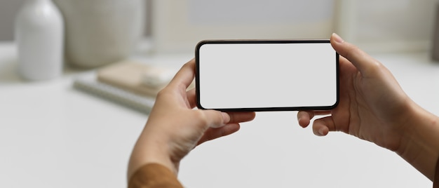Close up view of hands holding horizontal smartphone with clipping path at workspace in home office