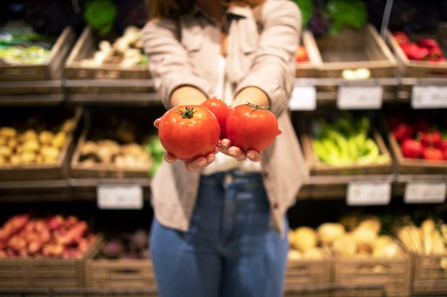 Close up view of hands holding tomatoes vegetables in supermarket