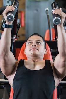 Close up view handsome asian male doing chest exercises