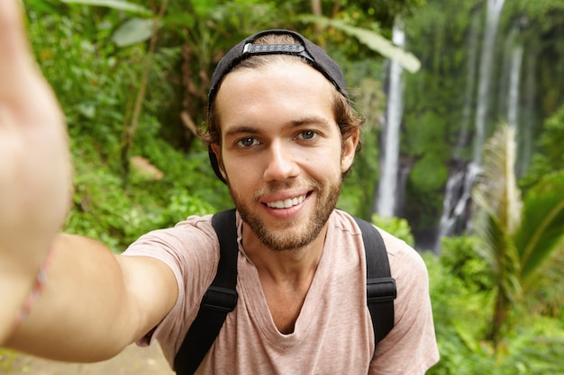 Close up view of handsome caucasian hiker wearing snapback looking with happy smile while taking selfie with amazing landscape with waterfall