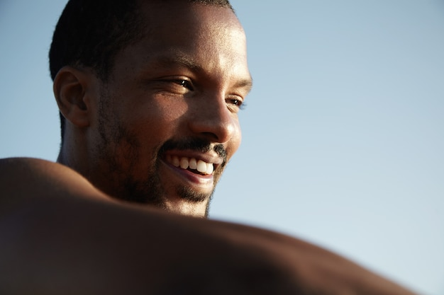 Close up view of handsome happy dark-skinned man with healthy skin and cheerful smile looking into distance