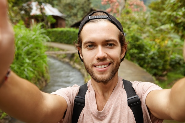 Close up view of happy face of attractive hiker with beard smiling while taking selfie