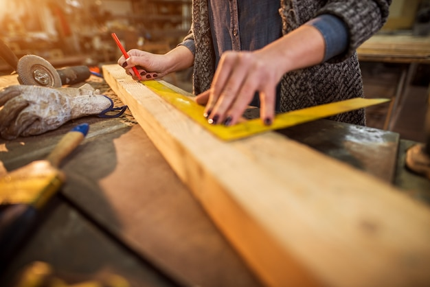 Close up view of hardworking professional carpenter working with a ruler and making marks on the wood