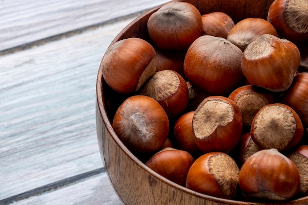 Close up view of hazelnuts in a bowl on wooden rustic