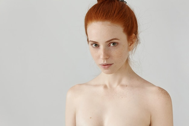 Close up view of head and shoulders of amazing redhead young woman with freckles